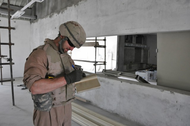 Jason Riharb, a civil engineer and contracting officer's representative with the Afghanistan Engineer District-South, makes notes during his inspection of an Afghan National Civil Order Police Patrol Battalion compound in Kandahar province.