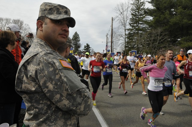 Sgt. Ezequiel Valencia, a human resources sergeant, with the 747 Military Police Company, Massachusetts Army National Guard, looks on as runners begin the 117th Boston Marathon, April 15, 2013, in Hopkinton, Mass. More than 400 Guardsman were on hand to help local law enforcement keep the route clear for an estimated 27,000 runners.
