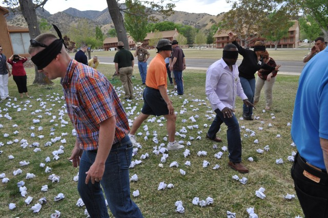 "Several members of the NETCOM staff attempt to navigate through a ""minefield"" of paper balls April 12. The exercise is designed to teach communications skills and focusing on a single set of instructions, even when there are distractions."