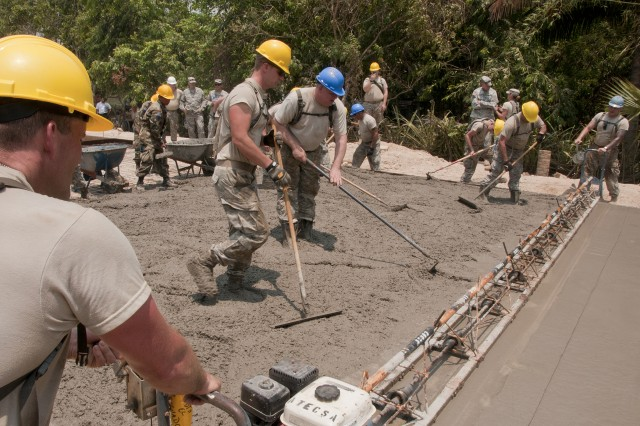 Salvadoran and U.S. soldiers grade recently poured concrete to avoid it from cracking at a site of a new school here, April 9. Soldiers of the 160th Engineer Company and their Salvadoran counterparts are working together during Beyond the Horizon-El Salvador to build three schools and three latrines in areas that need it.