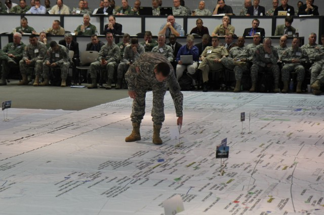 "FORT SAM HOUSTON, Texas "" Lt. Col Michael Grissom, operations officer for Defense Coordinating Element, Region VI, moves a placard on the floor map to indicate a change of location for his headquarters April 10 during the 2013 Hurricane Rehearsal at the Rehearsal of Concept facility here."