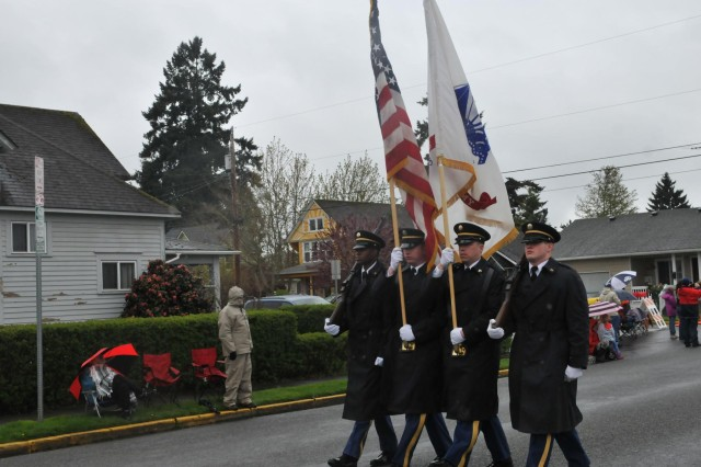 The I Corps Honor Guard marches through the streets of Puyallup during the Daffodil Parade, April 13, Puyallup, Wash. About 80,000-90,000 people showed up to celebrate the parade's 80th anniversary despite the cold weather, rain and freezing wind. (U.S. Army photo by Staff Sgt. Miriam Espinoza-Torres, 5th Mobile Public Affairs Detachment)