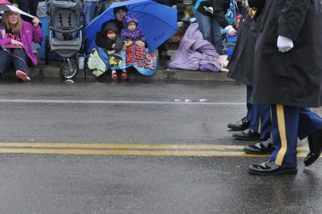 People attending the parade look up as the I Corps Color Guard marches by during the Daffodil Parade April 13, Puyallup, Wash. About 80,000-90,000 people showed up to celebrate the parade's 80th anniversary despite the cold weather, rain and freezing wind. (U.S. Army photo by Staff Sgt. Miriam Espinoza-Torres, 5th Mobile Public Affairs Detachment)