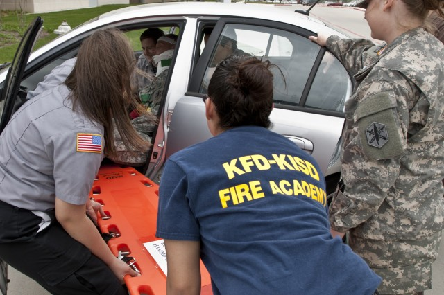 Emergency Medical Technician students at KISD Career Center work to extract 1st Sgt. David Doubek, Headquarters and Headquarters Company, 81st CA Bn, from a simulated car crash April 9 at the Career Center.  Specialist Courtney Rutan, a medic assigned to 81st CA Bn, looks on as she provides instruction to students.  (Photo by Army Staff Sgt Gregory Sanders, 85th CA Bde Public Affairs)