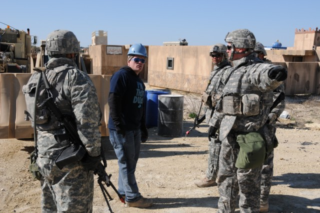 U.S. Army Sgt. 1st Class Seth White, right, a platoon sergeant with the 68th Engineer Company speaks with Pfc. Cody M. Vickers, center, role-playing as the foreman of a chemical company, about setting up defenses during a crisis management exercise at Fort Hood, Texas, March 25, 2013. In the scenario, a local chemical plant received intelligence of a potential terrorist attack. Vickers is a bridge crewmember, with the 74th Multi-Role Bridge Company. (Photo by Spc. Bradley J. Wancour, 13th PAD)