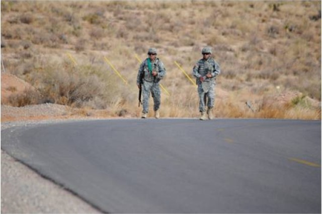 Staff Sgt. Fernando Terrazas, left, and his sponsor, Master Sgt. Manuel Rios, both members of 2nd Battalion, 363rd Infantry Regiment, Task Force Black Scorpion, 5th Armored Brigade, Division West, cross the finish line of the six-mile road march during the brigade's Noncommissioned Officer of the Year competition at McGregor Range, N.M., March 8. Terrazas won the competition and now will compete for the title of Division West NCO of the Year April 23-25 at Fort Hood, Texas. (Photo by Staff Sgt. Patricia Deal, 402nd Field Artillery Brigade, Division West, Public Affairs)