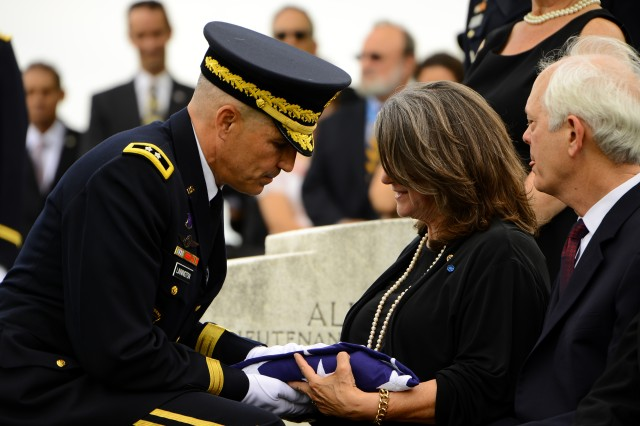 Maj. Gen. Michael S. Linnington, commanding general, Joint Force Headquarters-National Capital Region/Military District of Washington, hands a flag to Barbara (Bobbie) Broyles, during the funeral of her father, Lt. Col. Faith Jr., April 17, 2013, in Arlington National Cemetery, Va. He had been killed Dec. 1, 1950, near the Chosin Reservoir in North Korea.