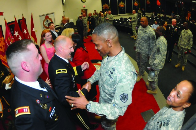 Brig. Gen. Edward Daly gets a congratulatory handshake and hug from Command Sgt. Maj. Sultan Muhammad after his promotion ceremony April 12 at Fort Lee's Ball Auditorium. Daly is the 37th chief of ordnance and commandant of the Ordnance School. Muhammad served under Daly as his regimental CSM and is currently the senior enlisted adviser for the Defense Logistics Agency at Fort Belvoir.
