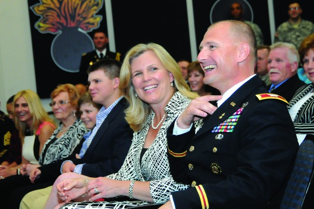 Brig. Gen. Edward Daly and his wife, Cathy, along with other family members, laugh at a pun of Maj. Gen. Kurt Stein during Daly's promotion ceremony April 12 at the Ball Auditorium.