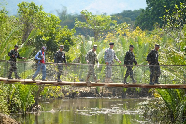 A group from Combined/Joint Civil Military Operations Task Force (CJCMOTF) walk across the new Tapuac footbridge, April 17, following a ribbon cutting ceremony conducted to officially open the footbridge to the local barangay. The project was one of seven engineering civic action projects (ENCAP) completed by Combined/Joint Civil Military Operations Task Force (CJCMOTF) units during Exercise Balikatan 2013. Balikatan is an annual Philippine-U.S. bilateral exercise. Humanitarian assistance and training activities enable the Philippine and American service members to build lasting relationships, train together and provide assistance in communities where the need is the greatest.