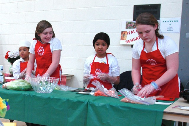 (From left)  Carlos Clavijo, 6, Shyann Stolo, 10, Iliana Clavijo, 8 and Samantha Devorak, 12 demonstrate how to make a Caesar salad with grilled chicken  during the annual 4-H Meal Appeal cooking contest held at the APG North (Aberdeen) youth center April 13.
