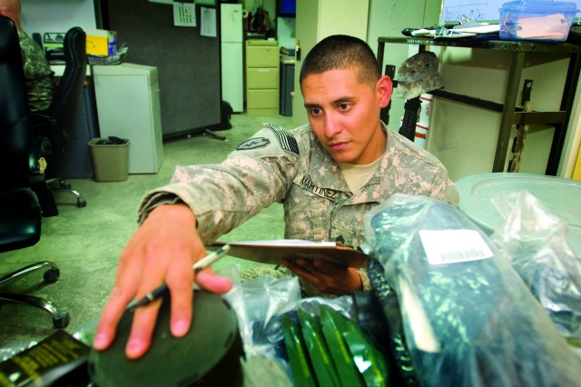 A special troops battalion supply sergeant inventories chemical protective equipment that had been turned in by a redeploying unit at Camp Victory, Iraq.