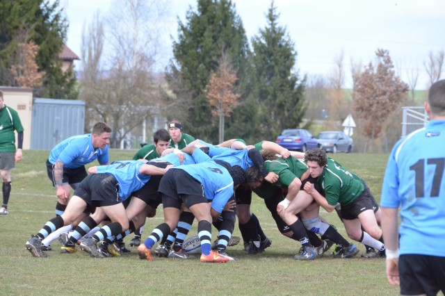"""The """"Black n Blue"""" amateur rugby team out of Storck Barracks -- in black and blue uniform -- grapples with a newly formed Wurzburg team in a scrum during a friendly match April 13 at Storck Barracks. Black n Blue won the match 101-0."""