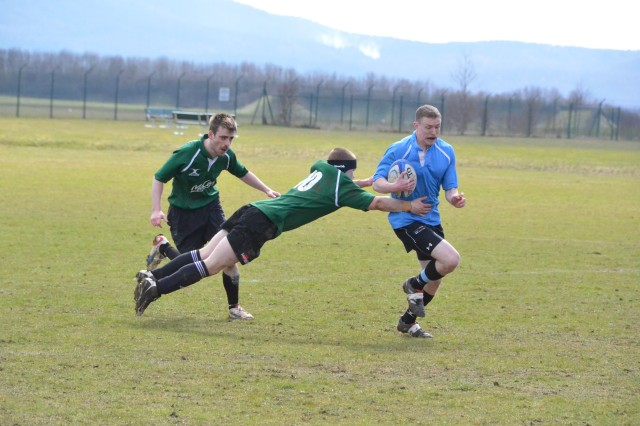 """A player from the Storck Barracks """"Black n Blue"""" rugby team, right, dodges a player from the Wurzburg team during a friendly match April 13 at Storck Barracks, Germany."""