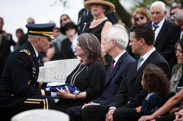 Maj. Gen. Michael S. Linnington, Joint Force Headquarters and National Capital Region - Military District of Washington hands the flag to Barbara Broyles, the daughter of U.S. Army Lt. Col. Don C. Faith Jr., during Faith's burial in Arlington National Cemetery, Va. April 17, 2013. Faith posthumously received the Medal of Honor for his actions during the Korean conflict's battle of Chosin Reservoir.