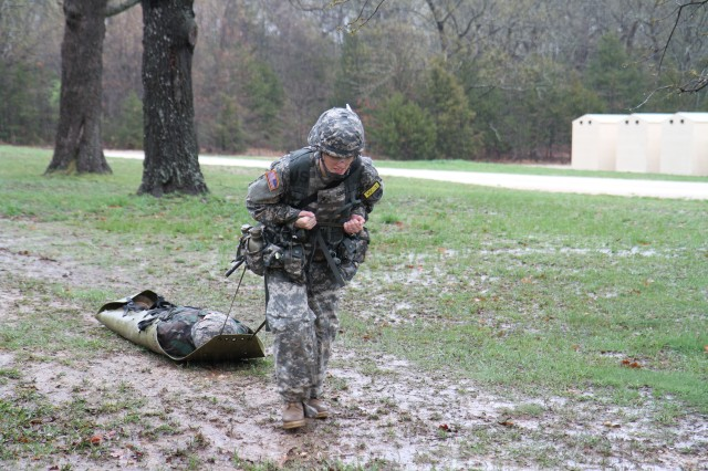 Spc. Cassie Kogle, 11-100 Military Intelligence Battalion, 100th Division, struggles to pull the 200-pound simulated injured Soldier during the 80th Training Command (TASS) 2013 Best Warrior Competition at Fort Leonard Wood April 18, 2013.