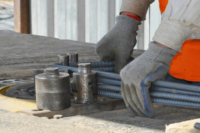 A construction worker bends rebar at the future installation for the 3rd Brigade, 205th Corps Afghan National Army in Zhari district, Afghanistan.