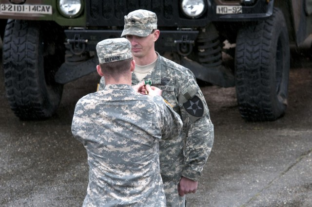 Maj. Donald Braman presents Sgt. Joseph Stout from 1st Squadron, 14th Cavalry Regiment, 3rd Stryker Brigade Combat Team, 2nd Infantry Division, the Army Commendation Medal with Valor during a ceremony April 12, 2013, at Joint Base Lewis-McChord, Wash.