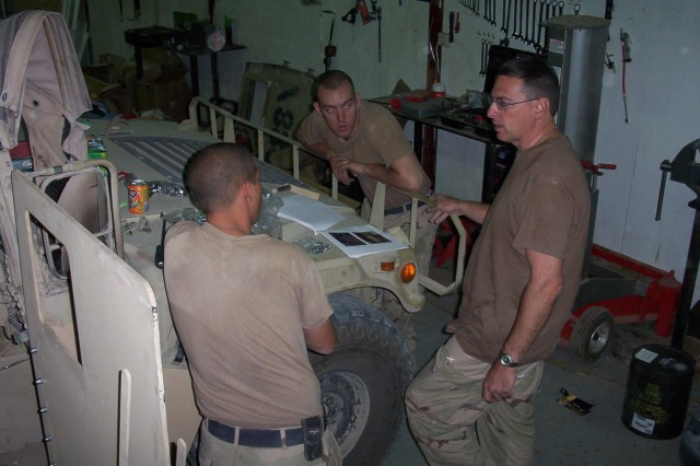 Michael Zoltoski (right), a civilian researcher with the Army Research Laboratory, gives step-by-step instructions on the installation of armor survivability kits at Camp Anaconda.