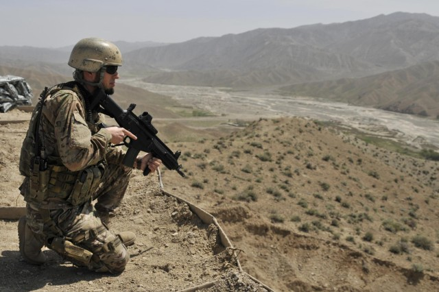 An Albanian special operations soldier surveys the area around an Afghan Border Police checkpoint overlooking a mountain pass near the Afghanistan-Pakistan border in the Spin Boldak district of Kandahar province, Afghanistan, April 1, 2013. The checkpoint was built to block an insurgent infiltration route.  (U.S. Army photo by Staff Sgt. Shane Hamann/Released)