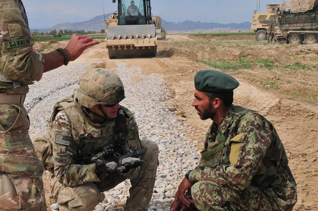 First Lt. Tomm Hickey, a platoon leader with the 229th Engineer Company, Wisconsin Army National Guard, talks with an Afghan engineer about gravel during a road construction project in the Panjwa'i district in Kandahar Province, Afghanistan, March 28, 2013. Soldiers with 1st Battalion, 38th Infantry Regiment, Combined Task Force 4-2 (4th Brigade Combat Team, 2nd Infantry Division), provided security for the engineers and their Afghan counterparts during the project.