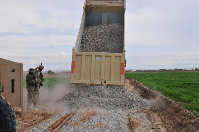 First Lt. Tomm Hickey, a platoon leader with the 229th Engineer Company, Wisconsin Army National Guard, and an Afghan engineer direct a dump truck delivering gravel during a road construction project in the Panjwa'i district in Kandahar Province, Afghanistan, March 28, 2013. Soldiers with the 1st Battalion, 38th Infantry Regiment, Combined Task Force 4-2 (4th Brigade Combat Team, 2nd Infantry Division), provided security for the engineers and their Afghan counterparts during the project.