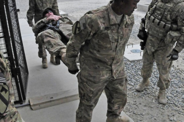 Sgt. First Class Ebony Jones (front), a health care specialist and native of Casey, Mo., helps Sgt. Jacob Culp, biomedical equipment specialist and native of Decatur, Ill., carry a role-playing casualty during a mass casualty exercise at the troop medical center on Forward Operating Base Gamberi, Afghanistan, April 8, 2013. Both are assigned to Company C, 27th Brigade Support Battalion, 4th Brigade Combat Team, 1st Cavalry Division, based out of Fort Hood, Texas.