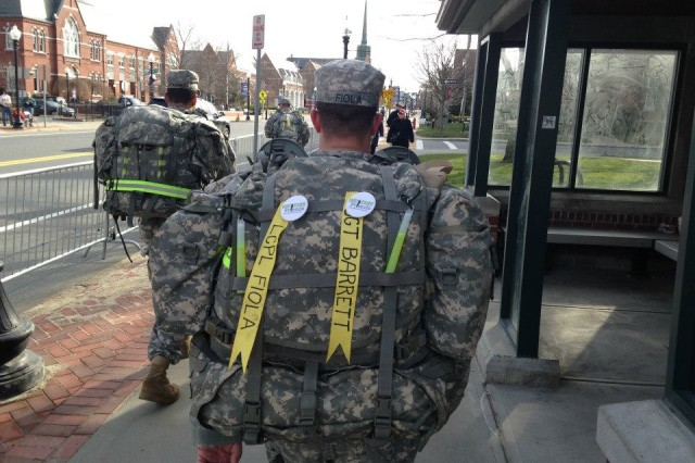 First Lt. Steve Fiola, of the Massachusetts Army National Guard, walks along the Boston Marathon course in Natick, Mass., April 15, 2013, bearing the names of fallen service members on his ruck sack. Fiola was one of the heroes at the finish line after the terrorist bombing.