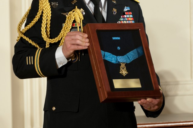 A Soldier holds the Medal of Honor that President Barack Obama posthumously awarded to Chaplain (Capt.) Emil J. Kapaun during a White House ceremony, April 11, 2013.