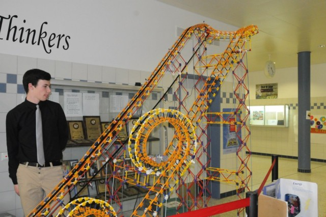 "Physics student Lucas Heath stands near ""Newton's Nightmare,"" the roller coaster constructed by the HMHS physics class for STEM night."