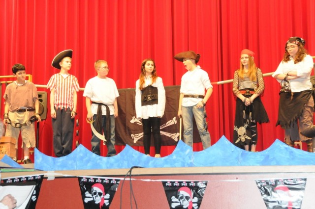 "Stowaway Verona McKinney (center) greets her fellow prisoners in the brig during the Hohenfels Elementary School's presentation of ""Pirates! the musical."""