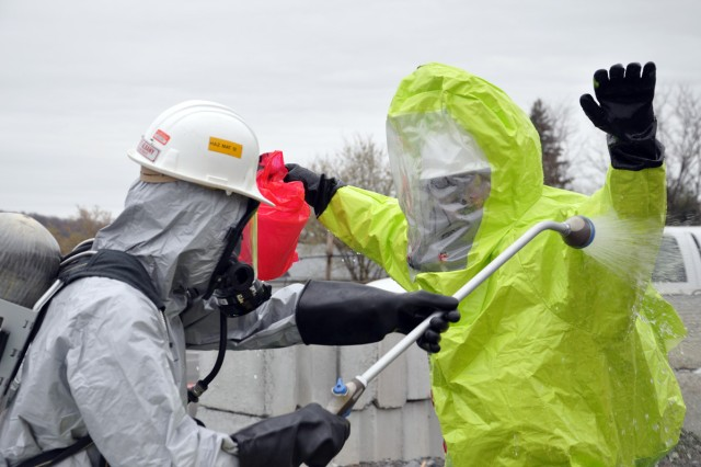 Arsenal HAZMAT team member, right, being washed down at the decon site.