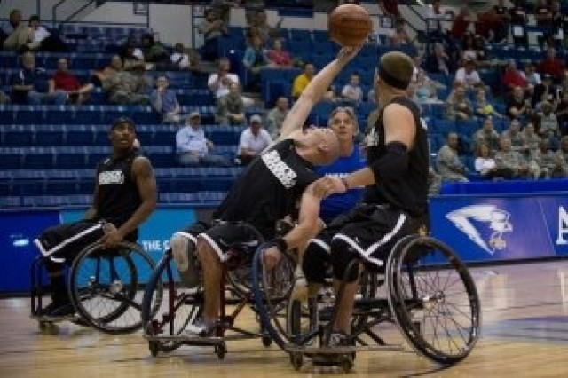 Sgt. Ryan McIntosh reaches for the ball to score during the wheelchair basketball competition at the 2012 Army Warrior Games in Colorado. He took home the gold medal in wheelchair basketball, silver medals in two track events, and a bronze medal in swimming.