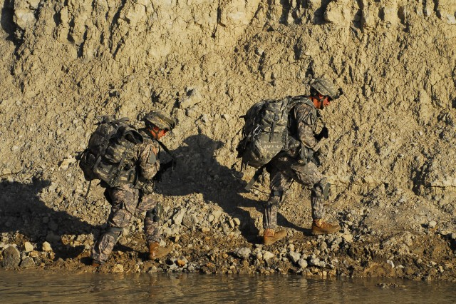 "Capt. Charles Elliot (left), commander of Company C, 115th ""Muleskinner"" Brigade Support Battalion of the Ironhorse Brigade and Capt. Christopher Vanderburg (right), commander of Company B, 1st ""Centurion"" Brigade, Special Troops Battalion, also of the Ironhorse Brigade, cross a stream while on a foot march during the Ironhorse Mungadai, April 9, 2013, at Fort Hood, Texas."