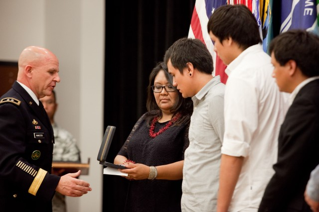 Maj. Gen. H. R. McMaster, commanding general, U.S. Army Maneuver Center of Excellence, presents Charlene Westbrook, the wife of Sgt. 1st. Class Kenneth Westbrook, and her three sons -- Zachary, Joshua and Joseph -- with her husband's Silver Star during a ceremony at Derby Auditorium at Fort Benning, Ga., April 19, 2013.