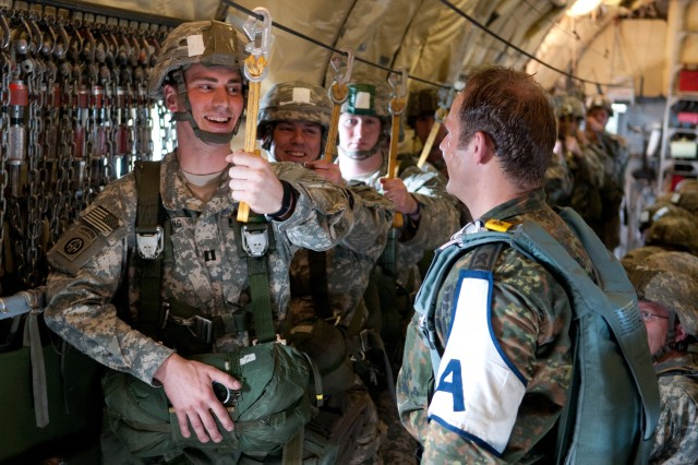 Capt. Randy J. Young, the logistics officer for 3rd Battalion, 319th Airborne Field Artillery Regiment, 1st Brigade Combat Team, 82nd Airborne Division, shares a laugh with Master Sergeant Dennis Hermerschmidt, a jumpmaster with the German army, April 17, 2013, aboard a C-160 Transall airplane above Fort Bragg, N.C., during Operation Federal Eagle, an annual joint airborne operation.