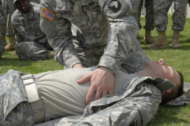 """Private Blakely Cornell, a medic assigned to the 1st Squadron, 33rd Cavalry Regiment, 3rd Brigade Combat Team """"Rakkasans,"""" 101st Airborne Division (Air Assault), demonstrates how to safely check for bleeding on the underside of a casualty during a brigade-consolidated Combat Life-Saver course April 18 at the Rascon School of Combat Medicine, Fort Campbell, Ky. The course was held to familiarize the unit's new Soldiers with the most recent medical standard operating procedures. (U.S. Army photo taken by Sgt. Alan Graziano, 3rd Brigade Combat Team, 101st Airborne Division)"""