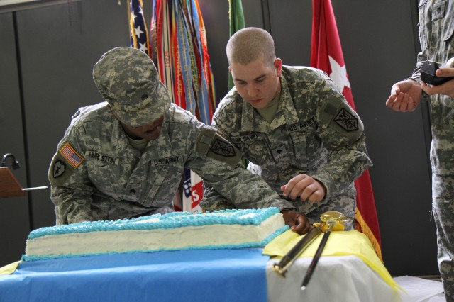 Sgt. Toni Hurlston and Spc. Zachary McDavid, both food service specialists for the 200th Military Police Command, prepare the cake for the 105th Birthday of the Army Reserve, April 23. (Army Reserve photo by Cpt. William Geddes)