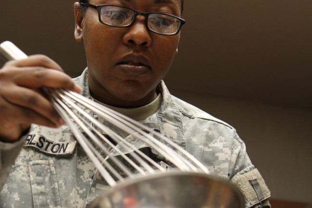 Sgt. Toni Hurlston, a food service specialist for the 200th Military Police Command, uses food coloring to get just the right shade of frosting to decorate the cake for the 105th Birthday of the Army Reserve, April 23 (Army Reserve photo by Cpt. William Geddes)
