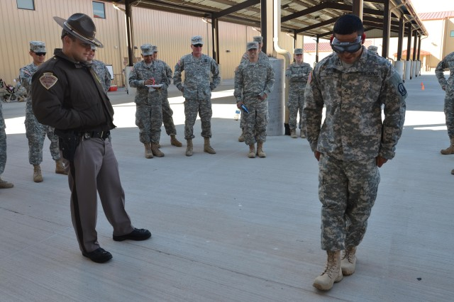 Oklahoma Highway Patrol Trooper Richard Danhorn monitors Pfc. Joel Rico as he attemps to walk straight will wearing 'drunk goggles' during the 3rd Battalion, 2nd Air Defense Artillery safety stand down day March 14, 2013, at Fort Sill.