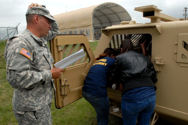 Specialist Peter Blanco, a medic with the 81st Civil Affairs Battalion, grades the performance of two Killeen Independent School District Career Center medical students as they prepare a simulated patient for vehicle extraction at the Fort Hood Medical Simulation Training Center April 23.  (Photo by Staff Sgt. David House, 85th Civil Affairs Brigade Public Affairs)