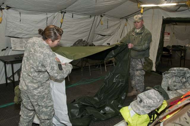 Sgt. Gina Pershong, executive assistant, 1st Medical Brigade, Headquarters and Headquarters Company, and Spc. Michael Jones, combat medic and command driver, 1st Med. Bde., HHC, stretch out a piece of the tent being used for the tactical operations center during a field training exercise in preparation for the Defense CBRNE (Chemical, Biological, Radiological, Nuclear, and High-Yield Explosive) Reactionary Force (DCRF) mission April 10. The TOC was a fully functioning workspace and simulated the facility that would be used during the DCRF mission. (Photo by Spc. Bradley J. Wancour, 13th PAD)