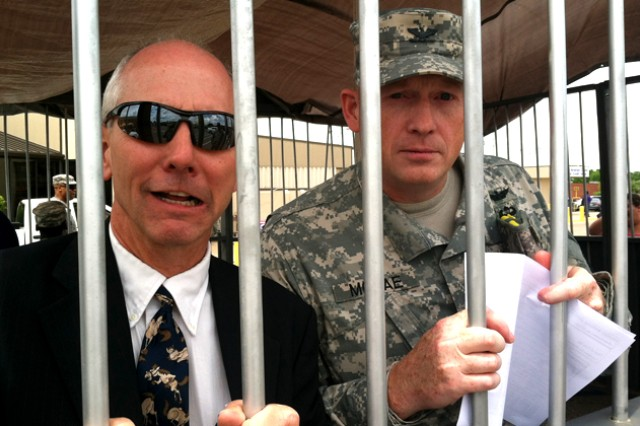 Justin O. Mitchell, Fort Rucker deputy garrison commander, and Col. Stuart J. McRae, Fort Rucker garrison commander, serve their time behind bars in a makeshift jail at the post exchange parking lot during Fort Rucker AER's Jail-a-Thon April 18.