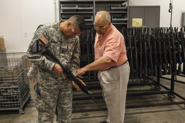 Jeff Bonner, chief of Anniston Army Depot's Weapons Division, discusses the installation's overhaul process for M4A1 machine guns with Command Sgt. Maj. Emmett Maunakea of Program Executive Office Soldier during his April 16 visit.