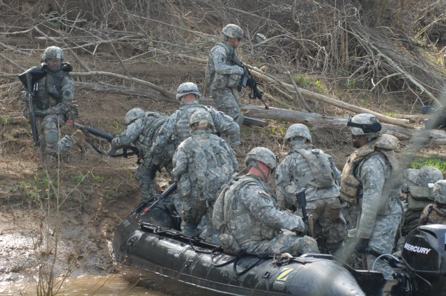 The 502nd Multi Role Bridge Company lived up to its name last week with an assault river crossing exercise that included a zodiac assault mission, air assault sling loads and construction of a seven-float improved ribbon bridge raft, at Fort Knox, Ky. Here, the far shore was secured before the bridge building could begin. The assault team transferred from the Zodiaks to land to encounter the opposition force and secure the area. Perimeter security was established quickly.