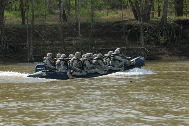 """The 502nd Multi Role Bridge Company lived up to its name last week with an assault river crossing exercise that included a zodiac assault mission, air assault sling loads and construction of a seven-float improved ribbon bridge raft, at Fort Knox, Ky. Here, the assault crew was transported from the secured portion of the exercise to the """"far shore"""" where the """"enemy"""" waited. Both shores must be secured against hostile fire before the bridge building can begin."""