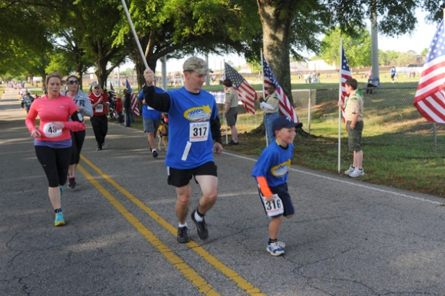 CW4 Wayne Grimes, B Company, 1st Battalion, 13th Aviation Regiment, with his son, Owen, carries an American flag during the second Survivors and Fallen Heroes 5k run April 20.