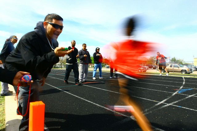 Volunteers Chief Warrant Officer 3 Andre Stewart (only hand visible), CW3 Sam Snyder, civilian Tito Griffith, CW2 Jason Timerson, CW3 Merle Delancey, and CW3 Brian Perkins time a sprint during the Hershey's Track and Field Games April 20, 2013, at Lawton High School, as CW3 Greg Koyle (far right) encourages runners. The 16 Soldiers in the 1st Battalion, 30th Field Artillery Warrant Officer Advanced Course volunteered at the meet for their class community project.