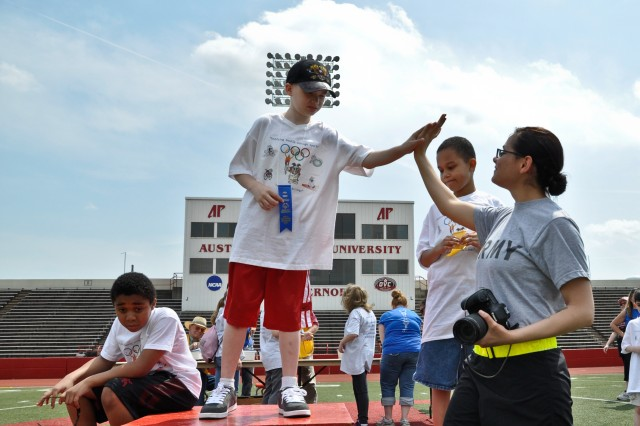 Spc. Angela Tedeski, a medic with Company C, 526th Brigade Support Battalion, 2nd Brigade Combat Team, 101st Airborne Division (Air Assault), congratulates students from Fort Campbell's Barsanti Elementary School as they receive their placement ribbons during the Area 12 Special Olympics, held at Clarksville's Austin Peay Stadium on April 18. The special needs students representing the Fort Campbell schools during the games attend Barkley Elementary, Barsanti Elementary, Lucas Elementary and Fort Campbell High School. (US Army photo by Sgt. Keith Rogers, 2nd BCT UPAR, 101st Abn. Div.)