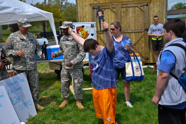 A student athlete representing Fort Campbell High School during the Area 12 Special Olympics raises his hands in celebration after receiving the War Fighter Award presented by the 526th Brigade Support Battalion, 2nd Brigade Combat Team, 101st Airborne Division (Air Assault), after the game's closing ceremonies held at Clarksville's Austin Peay Stadium, April 18. The volunteer Soldiers from the 526th BSB supported the Fort Campbell special needs students of Barkley Elementary, Barsanti Elementary, Lucas Elementary and Fort Campbell High School. (US Army photo by Sgt. Keith Rogers, 2nd BCT UPAR, 101st Abn. Div.)